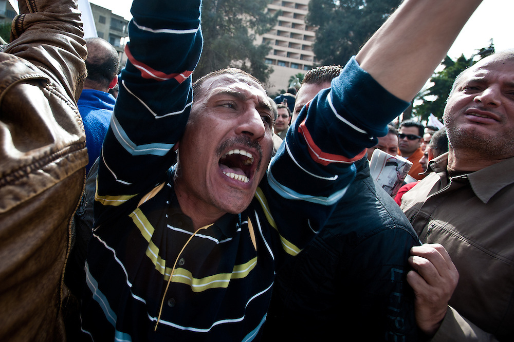 An anti-government protester shouts along to a chant on the approach to Tahrir Square, in the downtown area of Cairo, Egypt, where confrontations between supporters of President Hosni Mubarak and those calling for his resignation escalated to brutal violence this week.