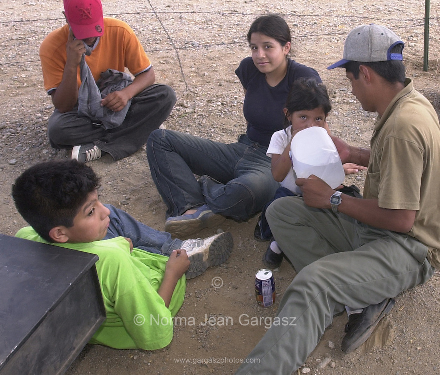 Illegal immigrants from Mexico, part of a group of 76, wait in Sells to be processed by Border Patrol agents.  Three of seven vehicles packed with entrants were stopped on Route 19 on the Tohono O'odham Reservation.  Four of the seven vehicles that crashed the border fence near the San Miguel gate managed to elude agents.  (PHOTO: NORMA JEAN GARGASZ)