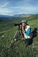 Woman looking through scope on Donjek Glacier hike in Kluane National Park