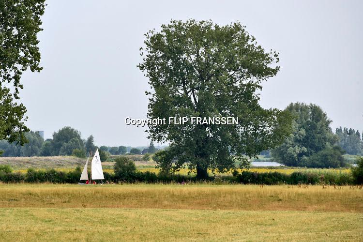 Nederland, Megen, 16-7-2019Langs de Maas tussen Grave en Lith moeten nog belangrijke aanpassingen gedaan worden door Rijkswaterstaat om de rivier klaar te maken voor de toekomst . Het heet hier de meanderende maas . Een zeilboot van de zeeverkenners vaart voorbij . Foto: Flip Franssen
