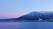 View of Tromsdalen in Northern Norway, in the winter blue light, seen on clear days after the sun stops rising for two months. Tromsø Bridge and Tromsdalen Church (Arctic Cathedral or Ishavskatredalen) are prominent in the view.