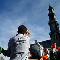 Nederland, Amsterdam , 27 april 2015.<br /> Koningsdag 2015.<br /> Op de foto: feestvierders op de Prinsengracht met Westertoren op de achtergrond.<br /> <br /> Foto:Jean-Pierre Jans