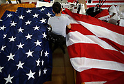 A worker sews together a U.S. Flag during manufacturing at the FlagSource plant in Batavia, Illinois.<br /> Photo by Jim Young for Bloomberg