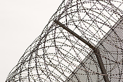 Security fence topped by razor wire UK prison