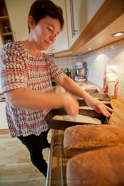 Ottersland Dahl family, of Gjettum, Norway (outside Oslo). Gunhild Valle Ottersland, 45, baking weekly bread for family. Model-Released.