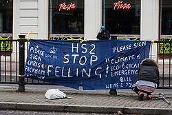 London, UK. 31 January, 2021. An anti-HS2 activist hangs a banner on Euston Road calling for HS2 Ltd to stop felling trees in Euston Square Gardens and for members of the public to sign a petition started by Chris Packham. Climbers from the National Eviction Team (NET) are currently dismantling a camp built by activists from HS2 Rebellion, five of whom in tunnels beneath, seeking to protect trees from felling in connection with the controversial HS2 high-speed rail project.