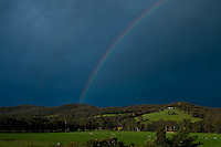 A rainbow punctuates an incredibly dark sky as a storm passes through the Yarra Valley in Victoria.