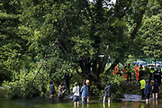 Environmental activists from HS2 Rebellion stand in the river Colne in Denham Country Park to try to prevent tree surgeons working with the National Eviction Team from cutting branches of an ancient alder tree above them as part of works for the HS2 high-speed rail link on 24th July 2020 in Denham, United Kingdom. A large security operation involving officers from the Metropolitan Police, Thames Valley Police, City of London Police and Hampshire Police as well as the National Eviction Team ensured the removal of the tree by HS2 despite the protests by activists.