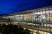 "Seen from the outside in early evening, the glass walls and glowing architecture of Heathrow Airport's Terminal 5, the largest free-standing building in the UK. Created by the Richard Rogers Partnership (now Rogers Stirk Harbour and Partners) and opened in 2008 after a cost of £4.3 billion, Terminal 5 has the capacity to serve around 30 million passengers a year. From writer Alain de Botton's book project ""A Week at the Airport: A Heathrow Diary"" (2009)."
