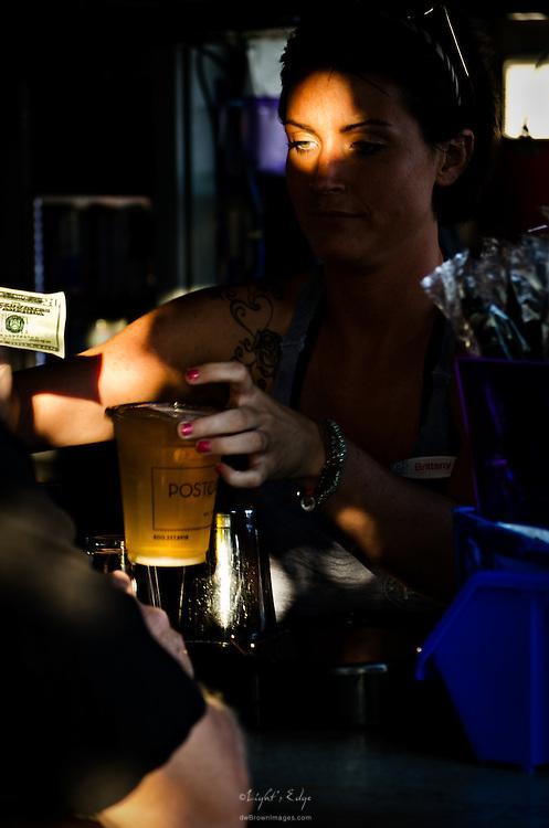 A bartender at The Postcard Inn beach bar checks a twenty dollar bill being offered for payment.