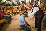 """13 JULY 2012 - FT DEFIANCE, AZ: Pastor ROGER TSOSIE, from the Window Rock Methodist Church, prays with people during the alter call at the 23rd annual Navajo Nation Camp Meeting in Ft. Defiance, north of Window Rock, AZ, on the Navajo reservation. Preachers from across the Navajo Nation, and the western US, come to Navajo Nation Camp Meeting to preach an evangelical form of Christianity. Evangelical Christians make up a growing part of the reservation - there are now more than a hundred camp meetings and tent revivals on the reservation every year. The camp meeting in Ft. Defiance draws nearly 200 people each night of its six day run. Many of the attendees convert to evangelical Christianity from traditional Navajo beliefs, Catholicism or Mormonism. """"Camp meetings"""" are a form of Protestant Christian religious services originating in Britain and once common in rural parts of the United States. People would travel a great distance to a particular site to camp out, listen to itinerant preachers, and pray. This suited the rural life, before cars and highways were common, because rural areas often lacked traditional churches.   PHOTO BY JACK KURTZ"""