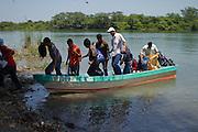 Migrants descend from a boat from San Pedro River, north of Guatemala in La Palma, south of Mexico. (Photo: Prometeo Lucero)