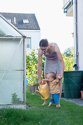 Mother and baby son holding a watering can in a lawn, Munich, Bavaria, Germany