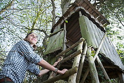 Low angle view of a teenage male hiker climbing on lookout tower in forest, Bavaria, Germany