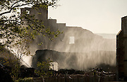 the ruin of a large building clouded in water damp and smoke after a totally destroying fire