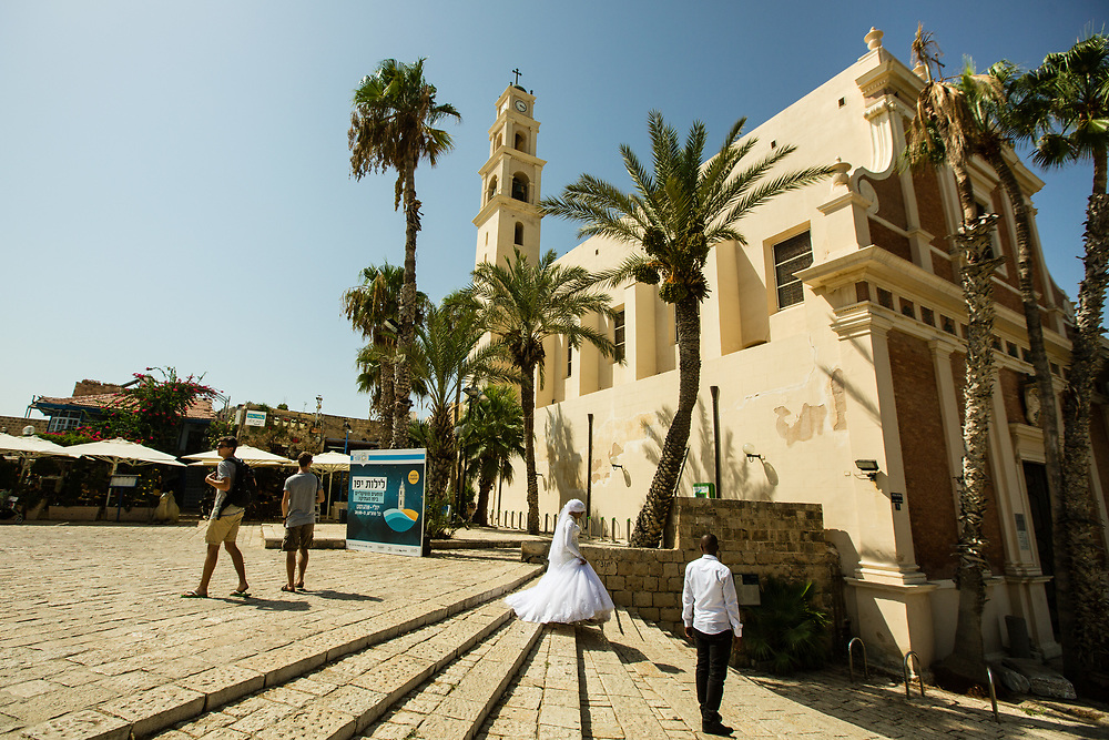 A bride and groom are seen during a pre-wedding photo session in Kdumim Square, at the Old City of Jaffa