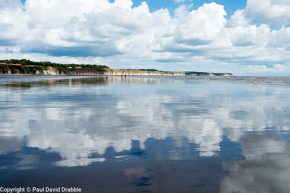 A couple walk two dogs  on smooth wet North Beach which reflects the clouds from the sky above in the sea side town of Bridlington West Yorkshire England<br /> <br />  4 August 2016<br />  Copyright Paul David Drabble<br />  www.pauldaviddrabble.photoshelter.com