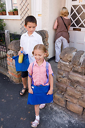 Mother and children leaving the house to go to school,