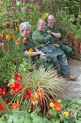 Men with learning difficulties on community allotment project resting on bench in garden ,