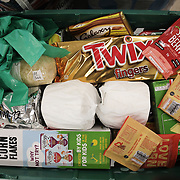 Workers and volunteers at Hackney Foodbank receive and organize food donations, 15th of December 2021, Hackney, East London, United Kingdom. A basket of a family food parcel. TheHackney Foodbank is part of a nationwide network of foodbanks, supported by The Trussell Trust, working to combat poverty and hunger across the UK. The food bank gives out three days emergency food supplies to families and individual who go hungry in the borrough. The food is all donated by individuals and the food donated is held in a small ware house where it is  sorted and packed for distribution.  More people than ever in Britain have turned to the food bank for help and in Hackney the need has gone up with 350% over the past two years.