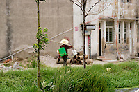 Female farmer with spray can on her back walking through a village in China.