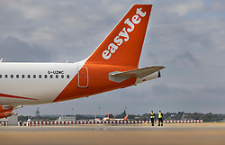 © Licensed to London News Pictures. 17/05/2021. Crawley, UK. Ground crew stand on the tarmac (R) as an EasyJet aircraft is prepared for departure at Gatwick Airport as step three on the roadmap out of lockdown begins. Travel to 12 countries on the green list is allowed from today. Holiday-makers returning home from green listed countries, including Portugal, Gibraltar and Iceland will not have to self-isolate on return. Various hospitality rules are also changing today - with pubs and restaurants allowed to serve seated customers indoors. Photo credit: Peter Macdiarmid/LNP