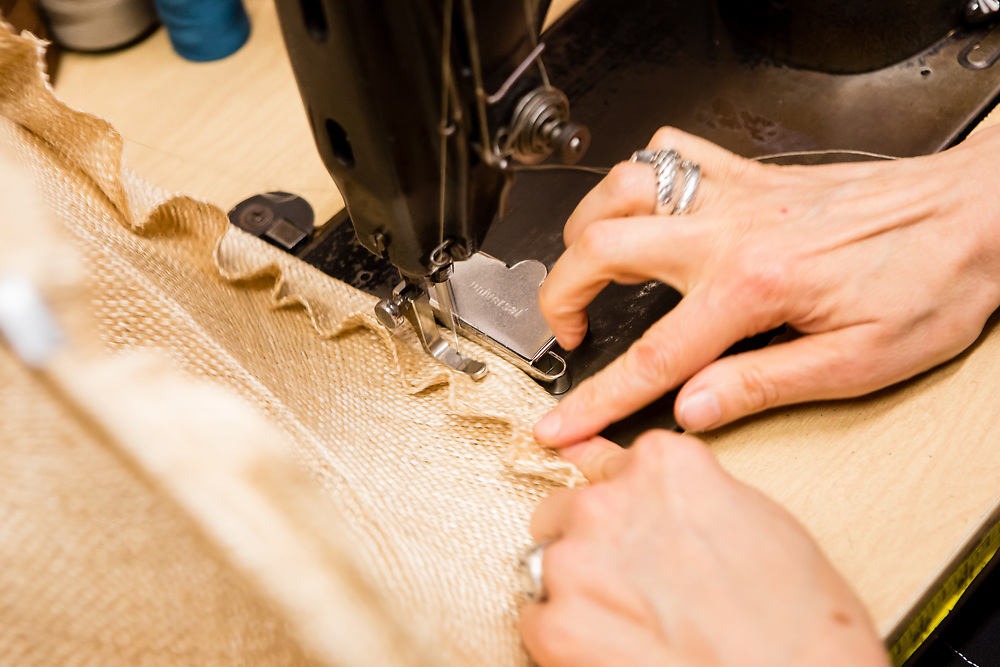 Sewing the edge of the brim of a straw hat. The edge is rolled over a thick monofilament line to help it keep its shape.