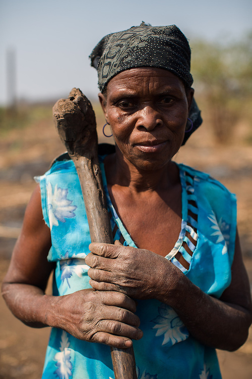 Cateme resettlement, Tete province, Mozambique. The family of Sadira Joaquim built a traditional kitchen beside the concrete house because the originally intended room was not suited for cooking...Over 700 families from the villages of Chipanga, Mitete, Malabue-Gombe and Bagamoyo were resettled to Cateme village, a Vale resettlement compound. Vale deliberately divided the communities in two with employed villagers moving to 25 de Setembro since it is closer to Moatize and the coal mine. The unemployed were resettled to Cateme, 40 km from the original town. While the most immediate problem of the community is the enormous distance to Moatize, their old habitat, they also suffer from unproductive farmland which can only be reached via a two hour walk, no access to markets and infrastructure and poorly constructed houses not fitted to the people's needs with temperatures inside reaching as high as 65° C due to the construction with tin clad roofs and missing isolation.