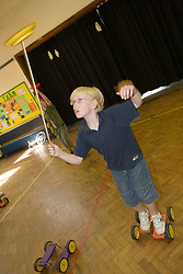 Young boy riding pedalo and practising with spinning top in school sports hall,