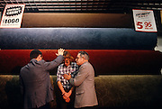 A young, vulnerable-looking youth stands close to two members of a local Evangelical church who are using a carpet warehouse as a temporary Ministry. Rolls of carpets and rugs are behind these Christians as the two officials practice the 'laying on of hands' to cleanse the soul of their young convert during a religious meeting in Newport, Wales. As the ceremony takes place when this boy is persuaded to accept Jesus into his life, two retail signs proclaim the prices and credit terms of the household items. The laying on of hands is a religious practice found throughout the world in varying forms. In Christian churches, this practice is used as both a symbolic and formal method of invoking the Holy Spirit during baptisms, healing services, blessings, and ordination of priests, ministers, elders, deacons, and other holy church ceremonies.