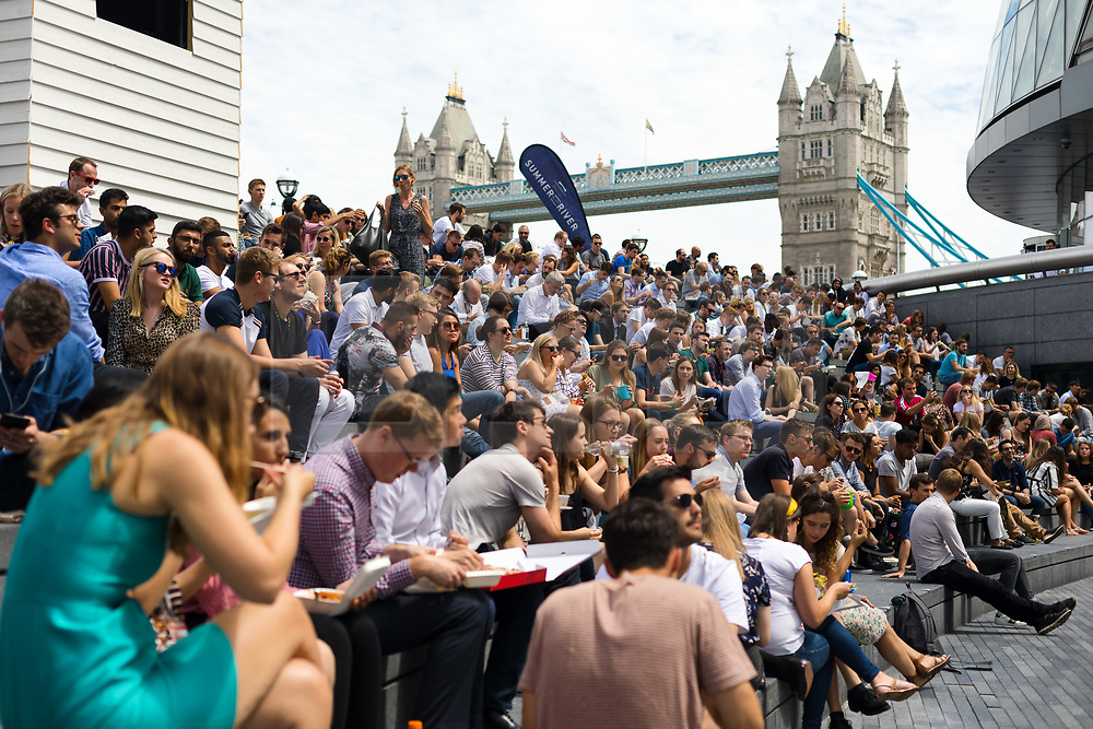 © Licensed to London News Pictures. 05/07/2019. London, UK.  Crowds of office workers and tourists enjoy the warm and sunny weather near Tower Bridge in London on Friday lunchtime. The UK continues to enjoy seasonally warm weather this week, but rain is forecast across the country during the next few days. Photo credit: Vickie Flores/LNP