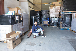 "© Licensed to London News Pictures. 07/05/2020. Salford, UK. Manager at Puro Medico SALAIMAAN MAJID (28) sits in the empty space in the warehouse from where the PPE was stacked up when it was stolen . £166,000 (one hundred and sixty six thousand pounds) worth of protective masks , which were destined for the NHS and care homes , have been stolen from a warehouse overnight (6th-7th May 2020) in what Greater Manchester Police are describing as a "" targeted burglary "" . Thieves cut the shutters at the loading bay of Puro Medico - which specialises in importing PPE such as masks from China and hand sanitiser from Poland - and stole several pallets of stock , which was loaded on to vans over a two hour period . Photo credit: Joel Goodman/LNP"