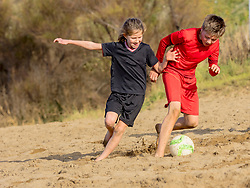 Girl and boy chasing soccer ball across sand