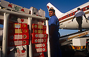 A Bahraini  baggage-handler employed by SABTCO pauses during his shift at Bahrain International airport. Having loaded luggage he is also about to put a cargo of fresh fruits on the conveyor belt and into the hold of an Egyptair Airbus. A colleague walks up the ramp towards the fuselage before the freight goes in before its imminent departure for Cairo, across the Mediterranean. It is another hot day in this Gulf State, a key hub airport in the region, providing a gateway to the Northern Gulf. The airport is the home for Gulf Air which provides 52% of overall movements and is also the half-way point between Western Europe and Asian destinations such as Hong Kong and Beijing. Picture from the 'Plane Pictures' project, a celebration of aviation aesthetics and flying culture, 100 years after the Wright brothers first powered flight, 1903..