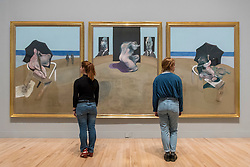 "© Licensed to London News Pictures. 26/02/2018. LONDON, UK. Staff members stand with ""Triptych"", 1974-1977, by Francis Bacon.  Preview of ""All Too Human"", an exhibition at Tate Britain which explores how artists in Britain have stretched the possibilities of paint in order to capture life around them.  The exhibition runs 28 February to 27 August 2018 and includes rarely seen works by Lucian Freud and Francis Bacon.  Photo credit: Stephen Chung/LNP"