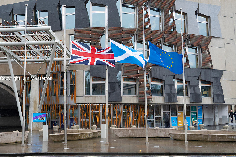 Edinburgh, Scotland, UK. 3 February 2021. Flags flying at half mast outside The Scottish Parliament at Holyrood in Edinburgh in tribute to the passing of Captain Sir Tom Moore who died yesterday at the age of 100.  Iain Masterton/Alamy Live News
