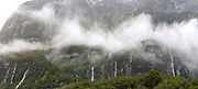 Waterfall pours into Milford Sound/Piopiotahi after a heavy rain; Fiordland National Park, New Zealand, along Highway 94
