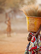 A young girl carries crops on her head through the streets of Bamako, Mali
