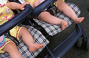 Twin baby?s bare feet hanging of a stroller