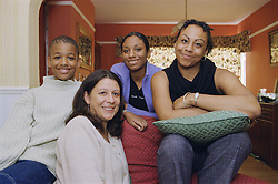 Mother sitting in living room with teenage son and daughters,