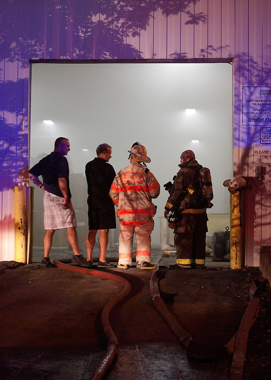 Mansfield, MA 09/13/2011.Firefighters stand in the open door of Miller Recycling in Mansfield during Tuesday night's 4 alarm fire..Wicked Local Photo by Alex Jones