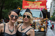"""Two young women in vaguely Russian-looking military caps pose in front of a truck in the parade that bears a sign reading """"From Russia with love leave hate behind."""""""