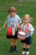 Brother and sister ages 4 and 3 playing drums at Selby Day Parade.  St Paul  Minnesota USA