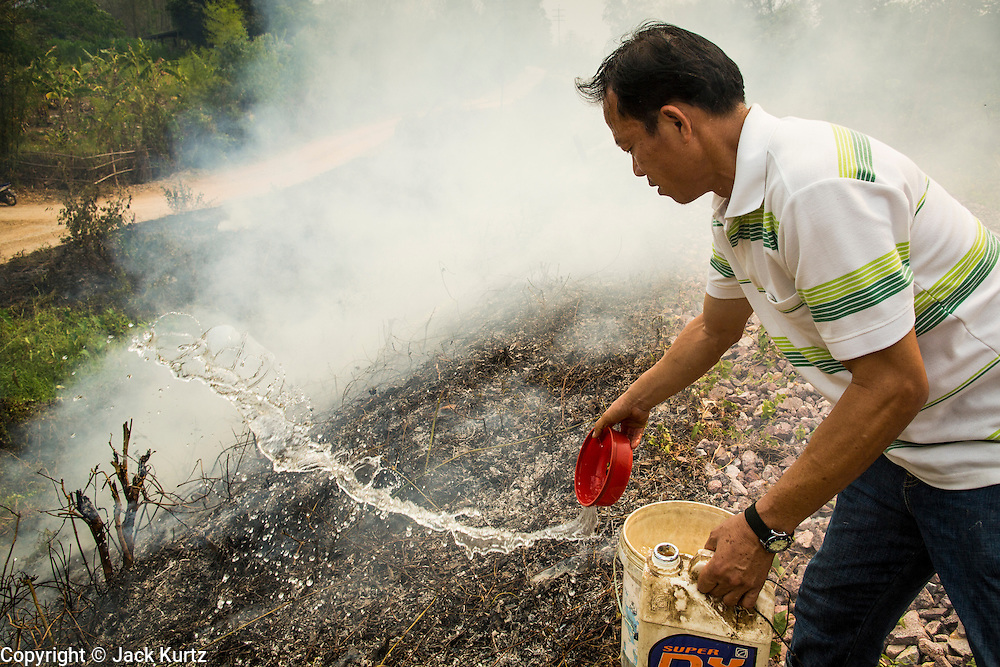 """09 APRIL 2013 - KHUNTAN, LAMPHUN, THAILAND:  An assistant village headman from Khuntan, Lamphun province, throws water on a grassfire burning on a roadside in the community. The """"burning season,"""" which roughly goes from late February to late April, is when farmers in northern Thailand burn the dead grass and last year's stubble out of their fields. The burning creates clouds of smoke that causes breathing problems, reduces visibility and contributes to global warming. The Thai government has banned the burning and is making an effort to control it, but the farmers think it replenishes their soil (they use the ash as fertilizer) and it's cheaper than ploughing the weeds under.     PHOTO BY JACK KURTZ"""
