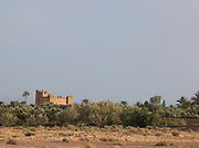 A kasbah towers above the palms of the Skoura Oasis in Morocco
