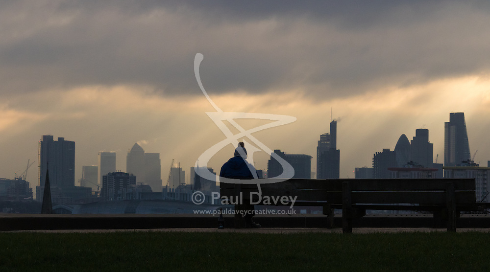 Primrose Hill, London, February 15th 2015. A man takes in the view of London's skyline on a chilly early morning on Primrose Hill, overlooking London's skyline.<br /> ///FOR LICENCING CONTACT: paul@pauldaveycreative.co.uk TEL:+44 (0) 7966 016 296 or +44 (0) 20 8969 6875. ©2015 Paul R Davey. All rights reserved.