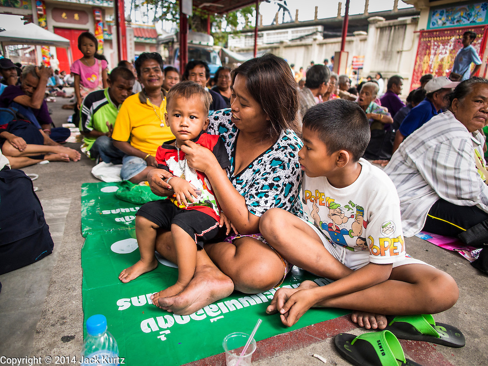 """09 AUGUST 2014 - BANGKOK, THAILAND:  A woman and her children wait for food to be handed out at the Ruby Goddess Shrine in the Dusit section of Bangkok. The seventh month of the Chinese Lunar calendar is called """"Ghost Month"""" during which ghosts and spirits, including those of the deceased ancestors, come out from the lower realm. It is common for Chinese people to make merit during the month by burning """"hell money"""" and presenting food to the ghosts. At Chinese temples in Thailand, it is also customary to give food to the poorer people in the community.        PHOTO BY JACK KURTZ"""