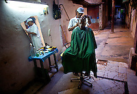 Cuban Barber gives haircut in alley at night.