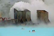Clouds of steam rise as people swim in the Blue Lagoon thermal pool, Iceland