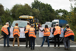 Insulate Britain climate activists block a slip road from the M25, causing long tailbacks on the motorway, as part of a new campaign intended to push the UK government to make significant legislative change to start lowering emissions on 13th September 2021 in Godstone, United Kingdom. The activists, who wrote to Prime Minister Boris Johnson on 13th August, are demanding that the government immediately promises both to fully fund and ensure the insulation of all social housing in Britain by 2025 and to produce within four months a legally binding national plan to fully fund and ensure the full low-energy and low-carbon whole-house retrofit, with no externalised costs, of all homes in Britain by 2030 as part of a just transition to full decarbonisation of all parts of society and the economy.